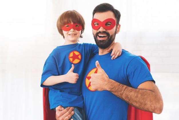 Père et fils dans les costumes rouges et bleus des super-héros. Photo Premium