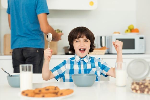 Père et fils déjeunent dans la cuisine claire Photo Premium