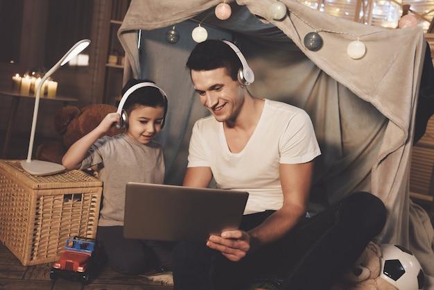 Père et fils écoutent de la musique sur un ordinateur portable le soir. Photo Premium