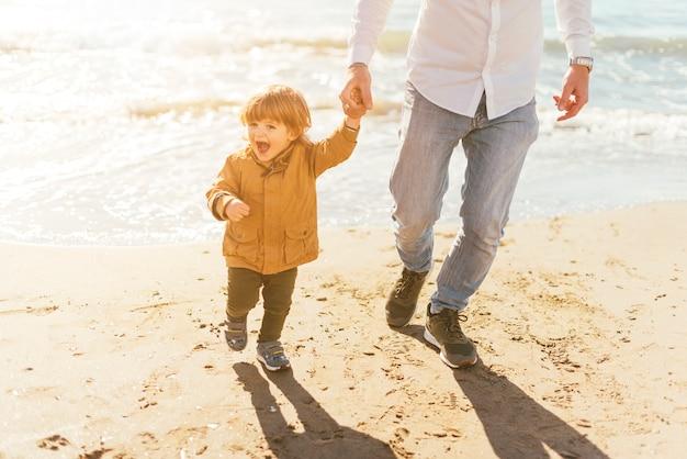 Père avec fils heureux sur la plage Photo gratuit