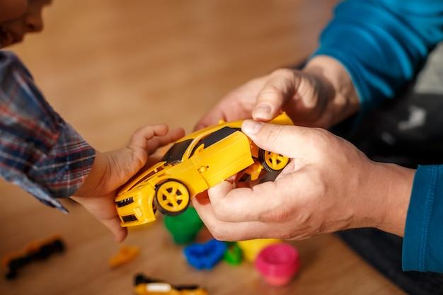 Père et fils jouant avec des machines à jouets Photo Premium