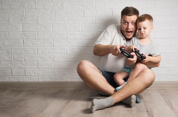 Père Et Fils Jouent Avec Leurs Contrôleurs Avec Espace De Copie Photo gratuit