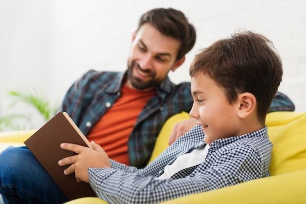 Père et fils lisant un livre Photo gratuit