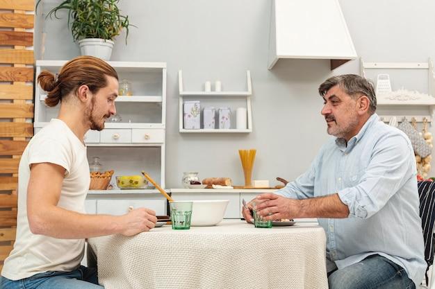Père et fils mangent ensemble Photo gratuit