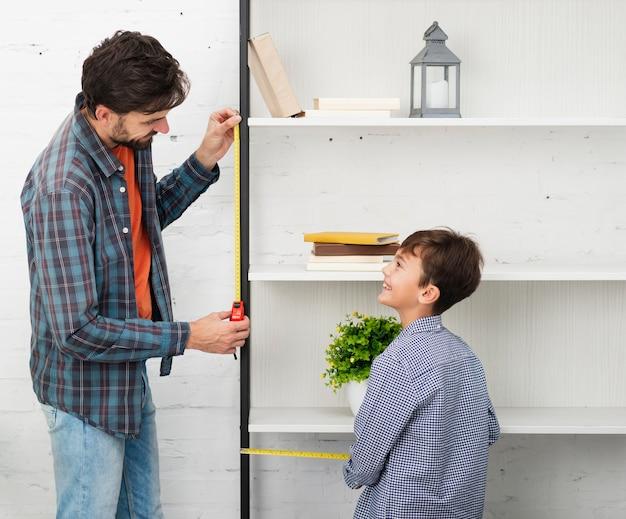 Père et fils mesurant une étagère Photo gratuit