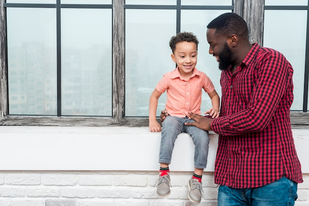 Père et fils noirs discutant au bord de la fenêtre Photo gratuit