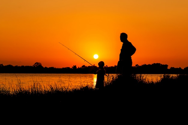 Père et fils pêchant dans la rivière sunset backgrond Photo Premium