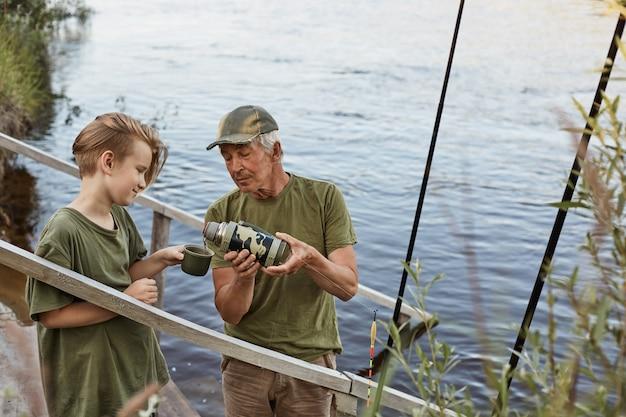 Père Et Fils Pêchant Dans La Rivière Photo gratuit