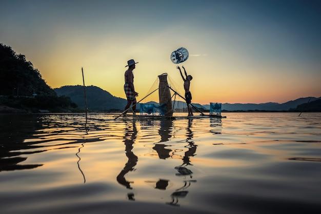 Père et fils, pêche en bateau sur le lac Photo Premium