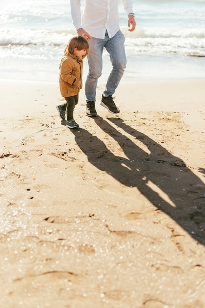 Père et fils sur la plage de sable jaune Photo gratuit