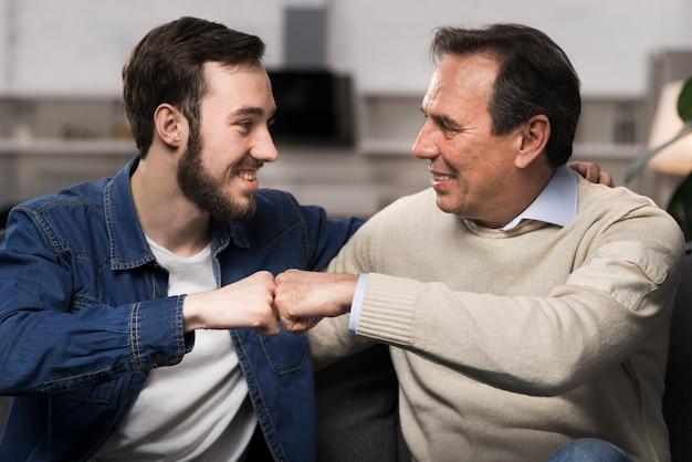 Père Et Fils Poing Se Cogner Dans Le Salon Photo gratuit