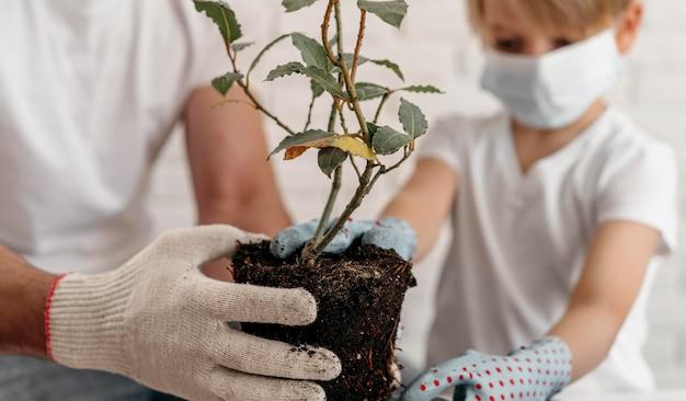 Père Et Fils Portant Des Masques Médicaux Et Apprenant à Planter Photo gratuit