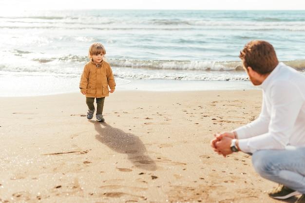 Père et fils près de la mer Photo gratuit