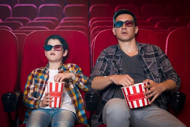 Père et fils en regardant un film au cinéma Photo gratuit