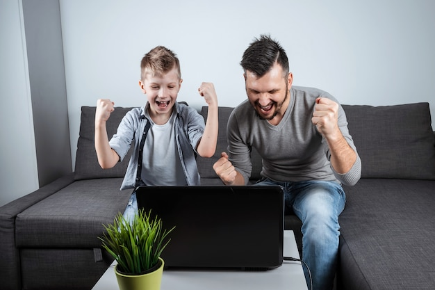 Père et fils en regardant le football dans un ordinateur portable à la maison Photo Premium