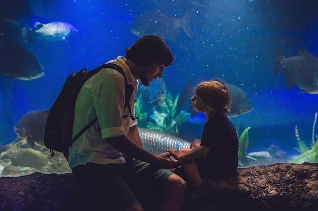 Père Et Fils Regardent Les Poissons Dans L'aquarium De L'océanarium Photo Premium