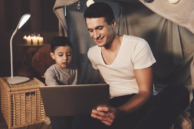 Père et fils regardent une vidéo sur un ordinateur portable le soir à la maison Photo Premium