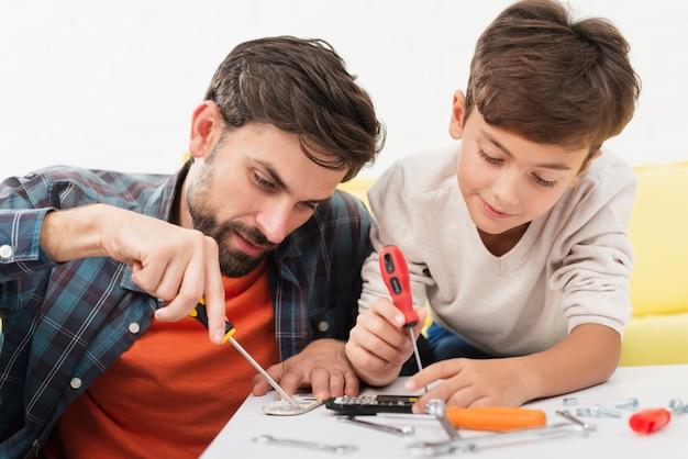 Père et fils réparant des autos miniatures Photo gratuit