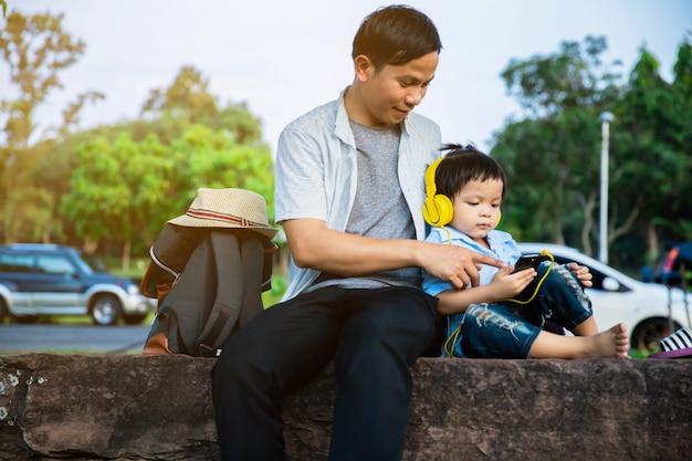 Père et fils s'asseoir et regarder le téléphone dans le parc Photo Premium