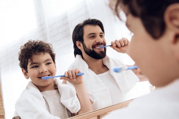Père et fils se brossent les dents avec une brosse à dents. Photo Premium