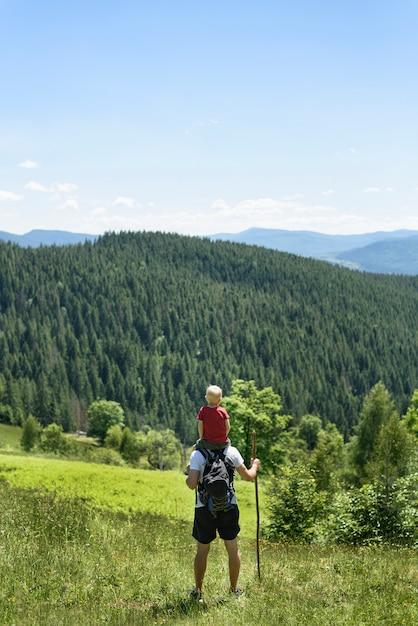 Père avec fils sur ses épaules debout avec le personnel dans la forêt verte, les montagnes et le ciel avec des nuages. vue arrière Photo Premium