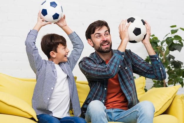 Père et fils tenant des ballons de football Photo gratuit