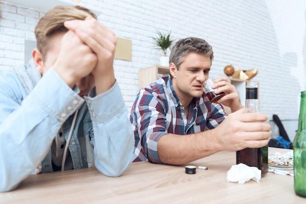 Père ivre est assis à table avec un verre. Photo Premium