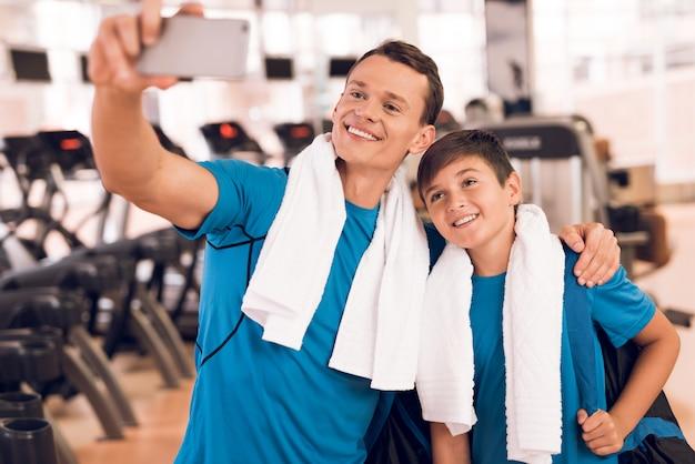 Père et jeune fils près de tapis de course dans un gymnase Photo Premium