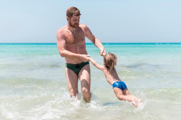 Père jouant avec un enfant dans la mer Photo gratuit