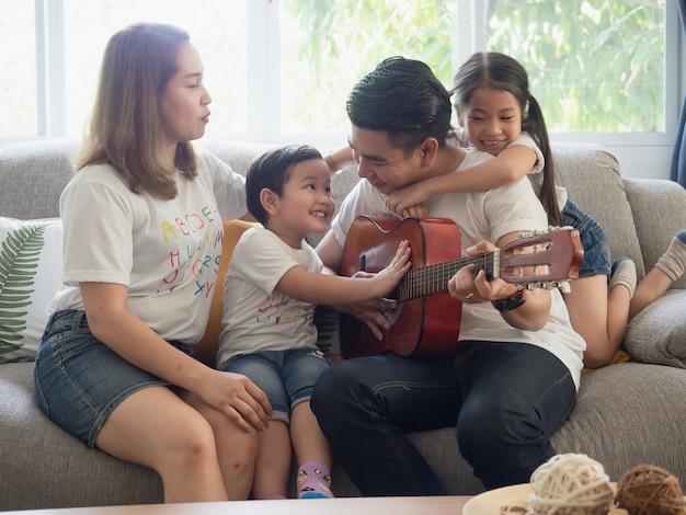 Père Jouant De La Guitare Pour La Famille Photo Premium