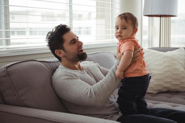 Père Jouant Avec Son Bébé Sur Un Canapé Dans Le Salon Photo gratuit