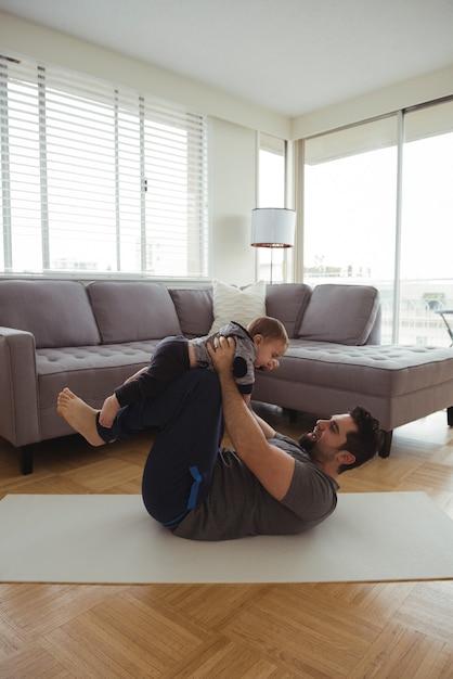 Père Jouant Avec Son Bébé Dans Le Salon Photo gratuit