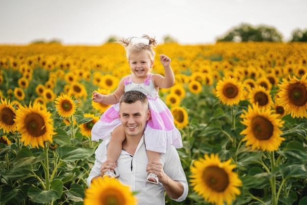 Père joue et tourne avec sa fille dans le champ de tournesol. Photo Premium