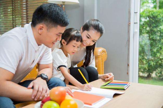 Père et mère enseigner aux enfants à faire leurs devoirs à la maison Photo Premium
