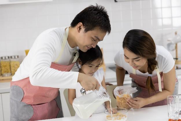 Père et mère préparent le petit déjeuner Photo Premium