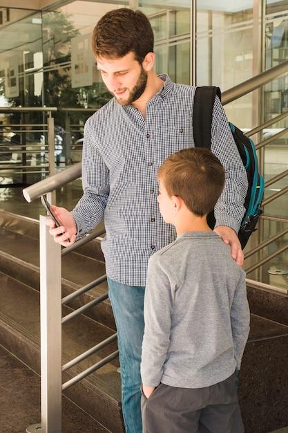 Père Montrant Quelque Chose à Son Fils Sur Un Téléphone Mobile Photo gratuit