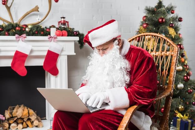 Père noël assis sur une chaise berçante et en tapant sur un ordinateur portable Photo gratuit