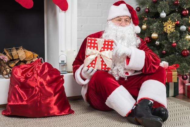 Père noël assis avec des coffrets cadeaux au sol Photo gratuit