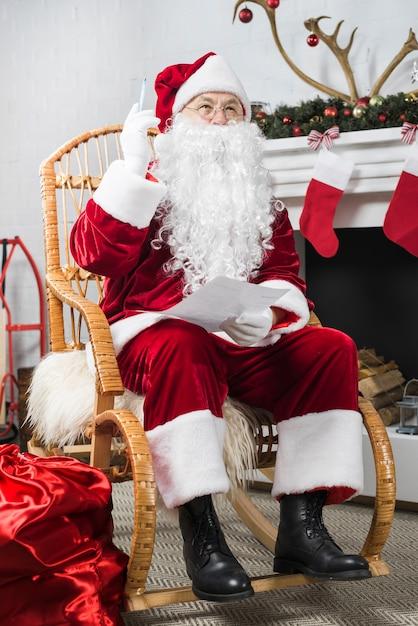 Pere Noel Assis Père Noël Assis Dans Une Chaise Berçante Avec Liste De Souhaits Et