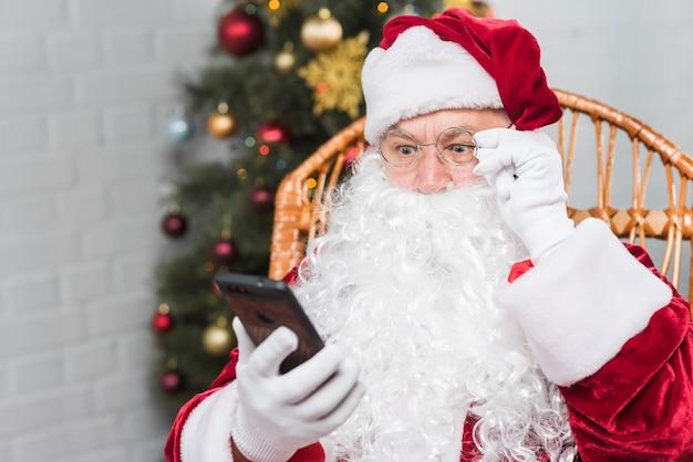 Père noël assis sur un fauteuil à bascule et regardant un téléphone Photo gratuit