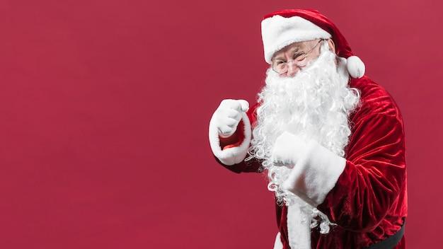 Père noël au chapeau rouge montrant les poings Photo gratuit