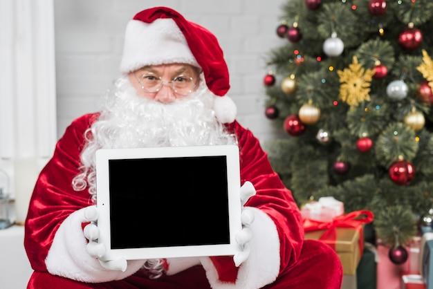 Père noël au chapeau rouge tenant la tablette en mains Photo gratuit