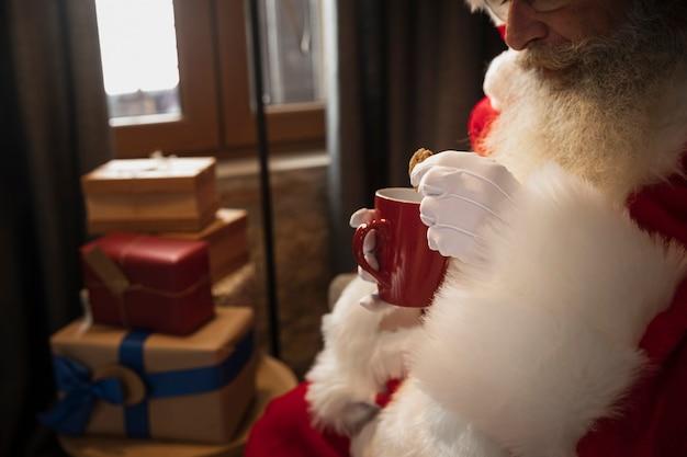 Père noël buvant une tasse de café Photo gratuit