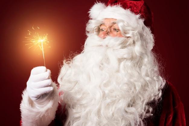Père Noël Avec Un Cierge Magique Sur Fond Rouge Photo gratuit
