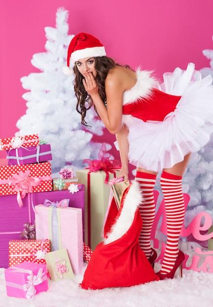 Père Noël Féminin Posant Avec Des Cadeaux Photo gratuit