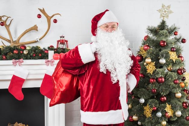 Père noël avec gros sac de cadeaux près de sapin de noël Photo gratuit