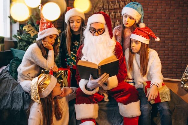 Père noël lisant un livre à un groupe d'enfants Photo gratuit