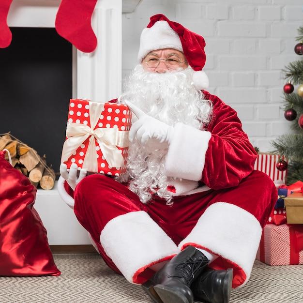 Père noël à lunettes assis avec des coffrets cadeaux sur le sol Photo gratuit