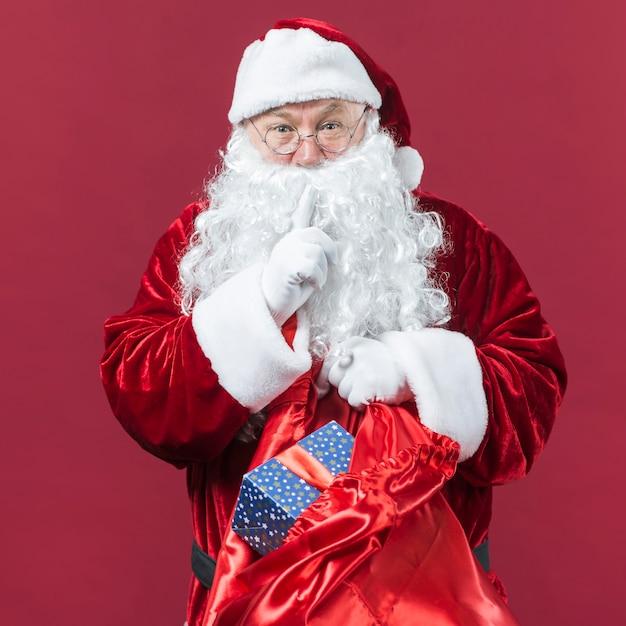 Père noël à lunettes avec sac de cadeaux montrant un geste secret Photo gratuit
