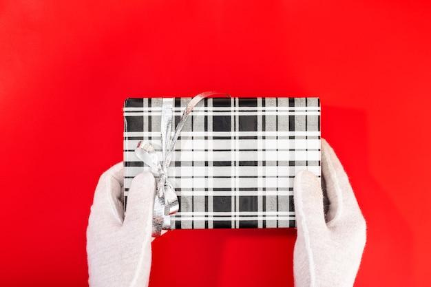 Père Noël Avec Des Mains Gantées Tenant Un Cadeau De Noël. Photo Premium